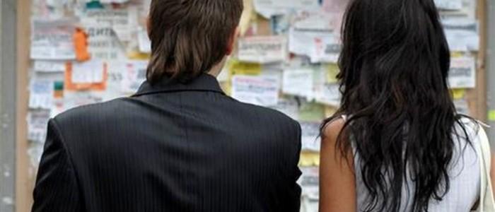 парень и девушка стоят возле доски объявлений